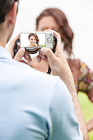 Young man photographing woman through digital camera in park