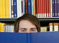 Young man peeking over opened book