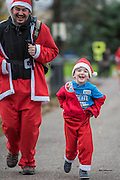 A young runner has trouble keeping his trousers up as he nears the finish - The London Santa Run 2015 in Battersea Park - 2,000 Santa's take part in an annual 'Red & White' bearded 'charge' around Battersea Park in a 6k festive charity fun run. The runners are of all ages and abilities and many run at a very slow pace but enjoy the event and the cause. The Santa Run is organised to raise funds for Disability Snowsport UK, a national charity helping people with disabilities to access the thrill of snowsports. The charity ensures that children and adults, with a range of disabilities (including cerebral palsy, Down's syndrome,  visual impairment and autism), can access programs across the UK to enable them to make friends, improve their confidence and have fun through a sport which they would otherwise be excluded from.