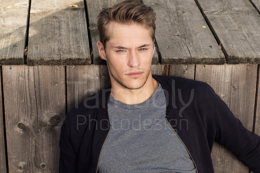 young man wearing casual outfit in the an urban wooden space.