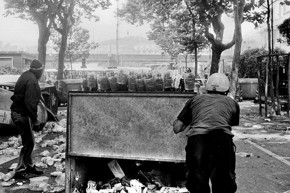 Genova, venerdì 20 luglio 2001. Giornata delle piazze tematiche. Corteo della disobbedienza civile. Manifestanti cercano di costruire barricate nei pressi di via Tolemaide, dopo l'assalto dei Carabinieri al corteo. Il personaggio sulla sinistra è di dubbia natura. In via Casaregis erano presenti uomini vestiti di nero che facevano la spola tra i manifestanti e le camionette dei carabinieri, avvicinandosi a queste oltre ogni limite di sicurezza. I giorni del G8 di Genova sono stati caratterizzati da un alto livello di infiltrazione da parte di agenti italiani e stranieri e di esponenti dell'estrema destra neofascista.