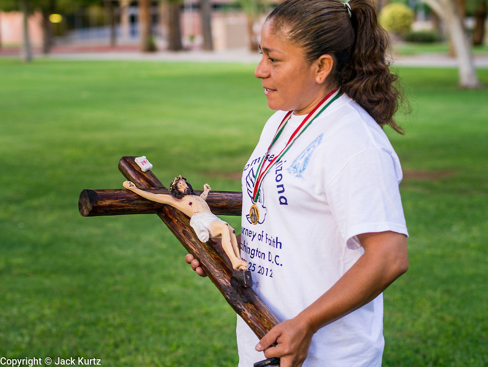 "19 JULY 2012 - PHOENIX, AZ:  GEORGINA SANCHEZ carries in a crucifix to the vigil at the Arizona Capitol during a vigil the first day of a class action lawsuit, Melendres v. Arpaio in Phoenix Thursday. The suit, brought by the ACLU and MALDEF in federal court against Maricopa County Sheriff Joe Arpaio, alleges a wide spread pattern of racial profiling during Arpaio's ""crime suppression sweeps"" that targeted undocumented immigrants. U.S. District Judge Murray Snow granted the case class action status opening it up to all Latinos stopped by Maricopa County Sheriff's Office deputies during the crime sweeps. The case is being heard in Judge Snow's court.  PHOTO BY JACK KURTZ"