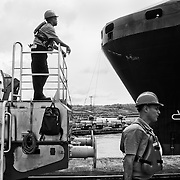 """MIRAFLORES LOCKS - PANAMA CANAL<br /> Photography by Aaron Sosa<br /> Panama City, Panama 2012<br /> (Copyright © Aaron Sosa)<br /> <br /> """"Canaleros"""" in task work. In the background can be seen one of the containers of a ship passing through the Panama Canal.<br /> <br /> The Panama Canal is an 77.1-kilometre (48 mi) ship canal in Panama that connects the Atlantic Ocean (via the Caribbean Sea) to the Pacific Ocean. The canal cuts across the Isthmus of Panama and is a key conduit for international maritime trade. There are locks at each end to lift ships up to Lake Gatun (26m (85ft) above sea-level) which was used to reduce the amount of work required for a sea-level connection. The current locks are 33.5m (110ft) wide although new larger ones are proposed.<br /> <br /> Work on the canal, which began in 1881, was completed in 1914, making it no longer necessary for ships to sail the lengthy Cape Horn route around the southernmost tip of South America (via the Drake Passage) or to navigate the dangerous waters of the Strait of Magellan. One of the largest and most difficult engineering projects ever undertaken, the Panama Canal shortcut made it possible for ships to travel between the Atlantic and Pacific Oceans in half the time previously required. The shorter, faster, safer route to the U.S. West Coast and to nations in and along the Pacific Ocean allowed those places to become more integrated with the world economy."""