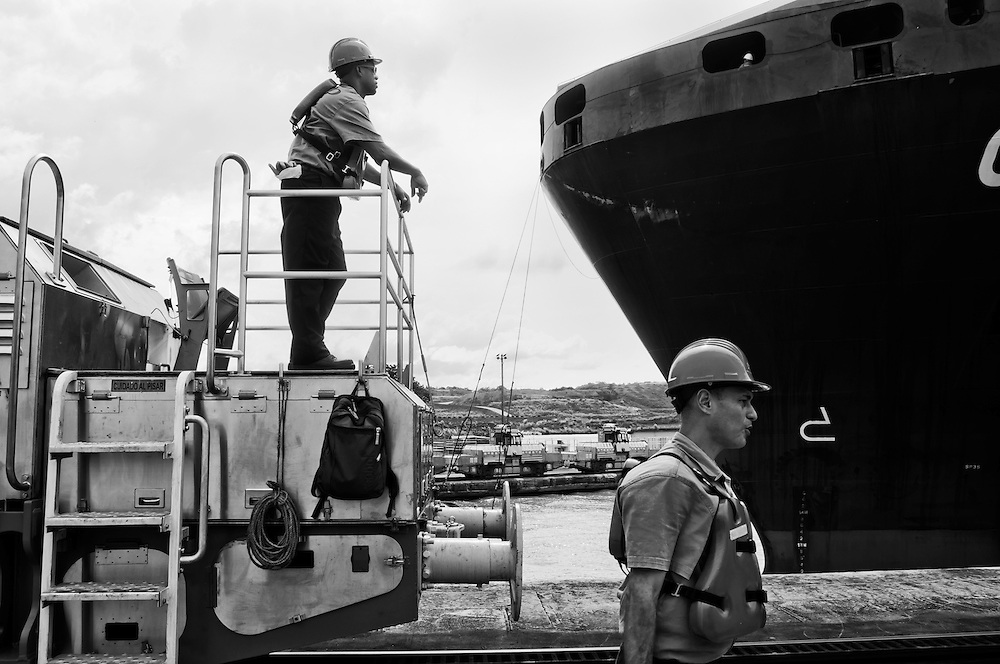 MIRAFLORES LOCKS - PANAMA CANAL<br /> Photography by Aaron Sosa<br /> Panama City, Panama 2012<br /> (Copyright &copy; Aaron Sosa)<br /> <br /> &quot;Canaleros&quot; in task work. In the background can be seen one of the containers of a ship passing through the Panama Canal.<br /> <br /> The Panama Canal is an 77.1-kilometre (48 mi) ship canal in Panama that connects the Atlantic Ocean (via the Caribbean Sea) to the Pacific Ocean. The canal cuts across the Isthmus of Panama and is a key conduit for international maritime trade. There are locks at each end to lift ships up to Lake Gatun (26m (85ft) above sea-level) which was used to reduce the amount of work required for a sea-level connection. The current locks are 33.5m (110ft) wide although new larger ones are proposed.<br /> <br /> Work on the canal, which began in 1881, was completed in 1914, making it no longer necessary for ships to sail the lengthy Cape Horn route around the southernmost tip of South America (via the Drake Passage) or to navigate the dangerous waters of the Strait of Magellan. One of the largest and most difficult engineering projects ever undertaken, the Panama Canal shortcut made it possible for ships to travel between the Atlantic and Pacific Oceans in half the time previously required. The shorter, faster, safer route to the U.S. West Coast and to nations in and along the Pacific Ocean allowed those places to become more integrated with the world economy.