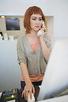 Young woman receptionist using the phone and the laptop in the hairdressers