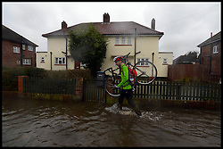 A residents in Egham carrying his bike through the water as floods hit the town, United Kingdom, Wednesday, 12th February 2014. Picture by Andrew Parsons / i-Images