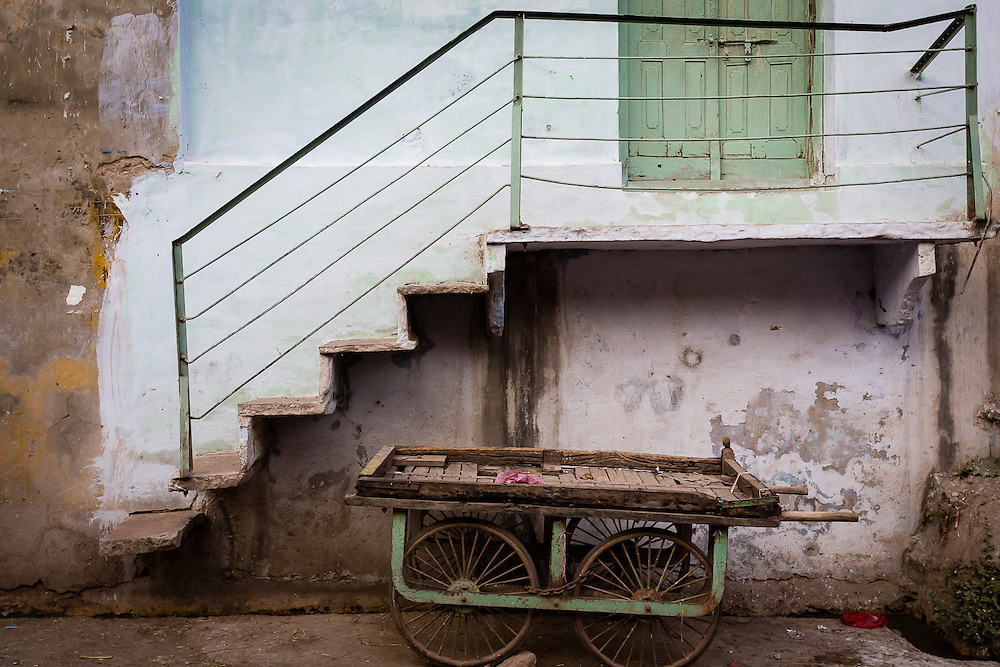 A cart under the stairs of a home in Bundi.