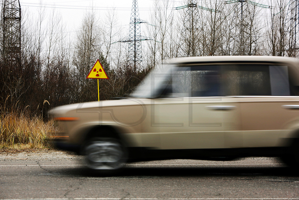 A car passes by a &quot;radioactive zone&quot; sign at a main road in Chernobyl area.<br /> This year several forest fires erupted near and in the 30 km (18.6 miles) exclusion zone around the plant, a problem to populations as this areas remain contaminated by radioactive particles that then spread through the air.