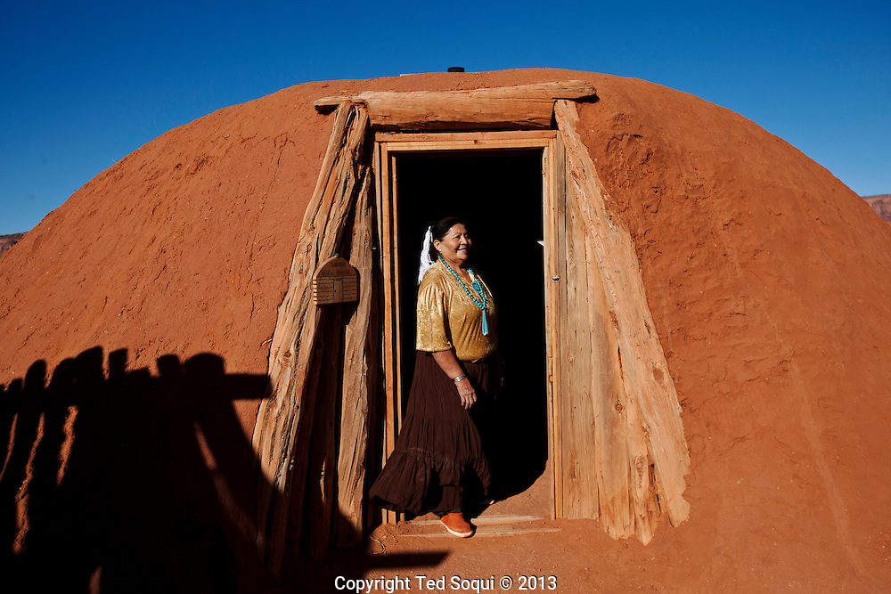 A Navajo woman stands in front of a hogan, a traditional living space for the Navajo people. The hogan can be taken apart and remade at different places. Many hogans are passed down generation to generation.