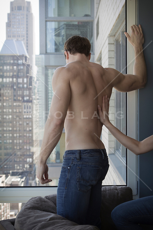 shirtless man at home in an apartment in New York City with a woman's hand on his back