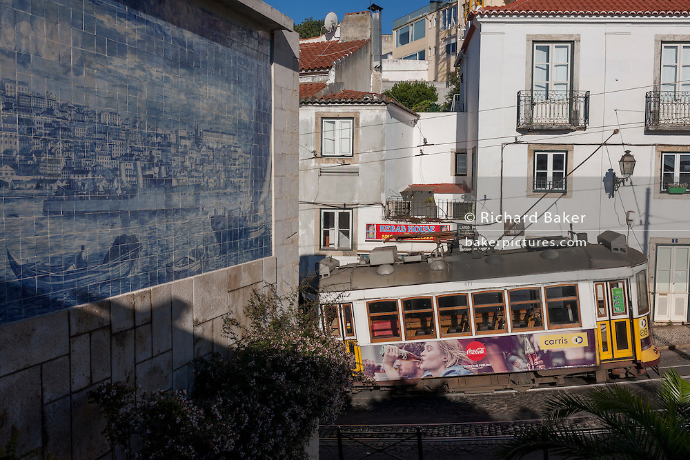 Passing some Azulejo tiles showing a city, a number 28 tram showing Coca Cola advertising rumbles up the gradient of a street in the Portugese capital, on 13th July 2016, in Lisbon, Portugal. The 28 is one of the trams not only used by the people of the capital but also of an increasing number of tourists who ride the entire route from Prazeres cemetery in the west of the city, to Rossio in the centre, after a loop through some of the most amazing streets and landmarks. So crowded is the 28, that older locals often can't sit down, having to stand over younger, inconsiderate tourist families who want a window seat for the entire journey - and back. Notices at termini remind visitors that this is a public service and to consider locals. (Photo by Richard Baker / In Pictures via Getty Images)