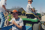 Boys on a lawnmower, one holding up his bottle of Mountain Dew drink, USA, 2000