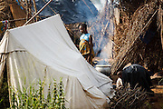 A woman stands between tents and basic shelters made of palm leaves where people now live after their homes were destroyed by floods in the village of Kpoto, Benin on Wednesday October 27, 2010.