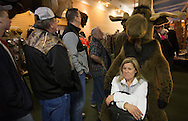 Sharon Ulrich of South Bend waits patiently after registering for the auction.  She found a nice spot with a moose to sit.  Hundreds of people gathered at 3 auction rings at Lunkers in Edwardsburg.  Portolese auctions was running the bank ordered liquidation of Lunkers merchandise and other assets.  The auction will run through Monday. Tribune Photo/SANTIAGO FLORES