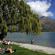 People relax on the edge of Lake Wanaka. Wanaka is  a year round destination set against the pristine alpine backdrop of Mount Aspiring National Park in Central Otago. South Island, New Zealand. 1st April 2011. Photo Tim Clayton
