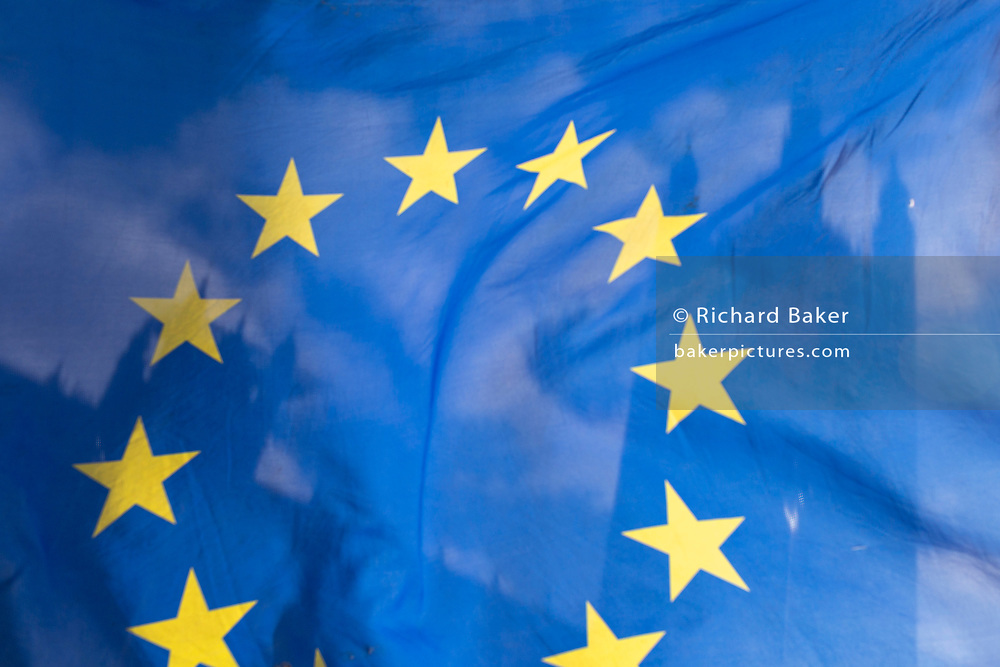 As Prime Minister Theresa May negotiates further Britain's exit from the European Union in Brussels, the UK parliament is seen through the yellow stars of the EU flag, flying as part of an anti-Brexit protest opposite the Houses of Parliament, on 7th February 2019, in Westminster, London England.