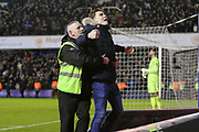 Millwall fan celebrates on the pitch with a steward during the The FA Cup fourth round match between Millwall and Everton at The Den, London, England on 26 January 2019.