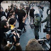 Protesters and riot police on Syntagma square, Athens. <br /> <br /> Following the murder of a 15 year old boy, Alexandros Grigoropoulos, by a policeman on 6 December 2008 widespread riots, protests and unrest followed lasting for several weeks and spreading beyond the capital and even overseas<br /> <br /> When I walked in the streets of my town the day after the riots I instantly forgot the image I had about Athens, that of a bustling, peaceful, energetic metropolis and in my mind came the old photographs from WWII, the civil war and the students uprising against the dictatorship. <br /> <br /> Thus I decided not to turn my digital camera straight to the destroyed buildings but to photograph through an old camera that worked as a filter, a barrier between me and the city.