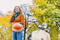 Portrait mature beautiful woman talking on smartphone and holding helmet while standing next to her motorbike in park