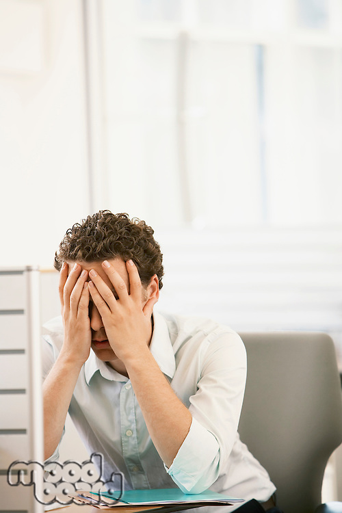 Stressed mid-adult male office worker sitting in cubicle head in hands