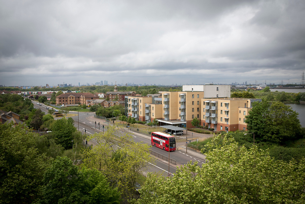 A red London bus drives down the A2041, passing the shopping area of Thamesmead, Greenwich, London. UK.  (photo by Andrew Aitchison / In pictures via Getty Images)