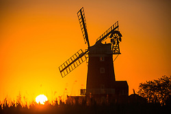 © Licensed to London News Pictures. 02/07/2018. Cley Next The Sea UK. The sun rises this morning behind the 18th Century Cley Windmill in the village of Cley Next The Sea on the Norfolk coast as the UK heatwave continues. Photo credit: Andrew McCaren/LNP