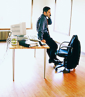 Businessman talking on phone, leaning against desk in bare office