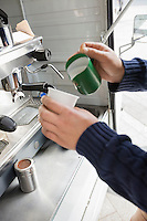 Cropped image of man pouring milk in cup at mobile coffee shop