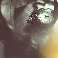 close up shot of a pocket watch in black and white with golden glow