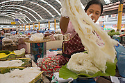 "24 FEBRUARY 2008 -- MAE SOT, TAK, THAILAND: A Burmese woman packages Burmese rice noodles in the Burmese market in Mae Sot, Thailand. There are millions of Burmese refugees living in Thailand. Many live in refugee camps along the Thai-Burma (Myanmar) border, but most live in Thailand as illegal immigrants. They don't have papers and can not live, work or travel in Thailand but they do so ""under the radar"" by either avoiding Thai officials or paying bribes to stay in the country. Most have fled political persecution in Burma but many are simply in search of a better life and greater economic opportunity.  Photo by Jack Kurtz"