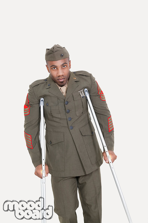 Portrait of an African American US military officer with crutches over gray background