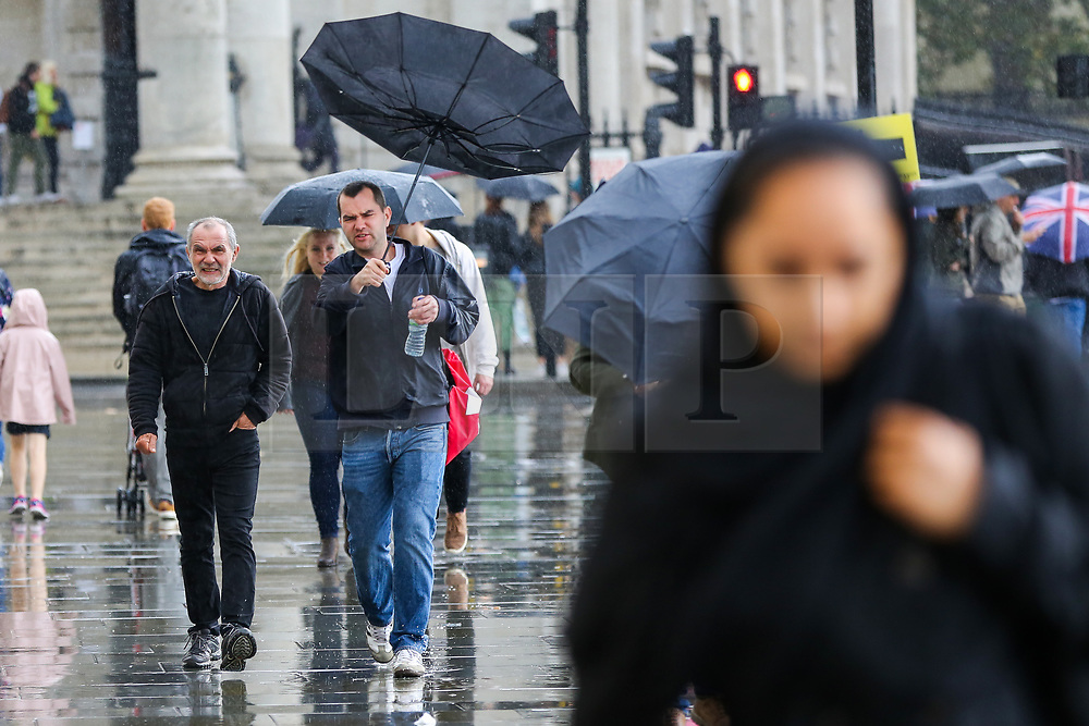 © Licensed to London News Pictures. 27/09/2019. London, UK. A man struggles with his umbrellas during heavy downpour in London. According to the Met Office, this weekend is set to be washout with over 2o hours of rainfall in the capital. Photo credit: Dinendra Haria/LNP. Photo credit: Dinendra Haria/LNP