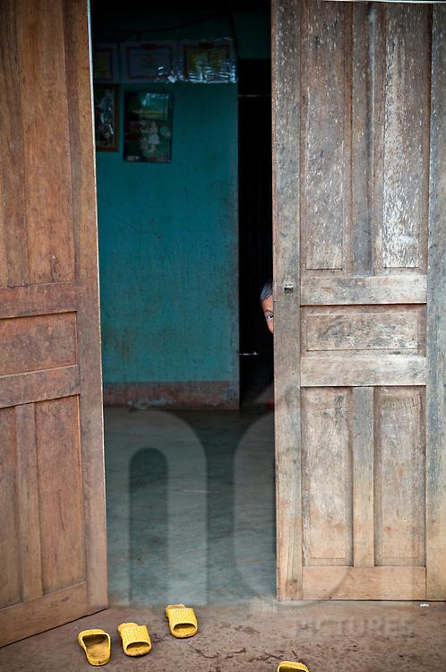 A kid hide behind a wooden door and looks at the photographer. Pleiku area, Vietnam, Asia