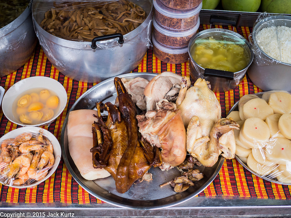 28 AUGUST 2015 - BANGKOK, THAILAND: A banquet of food left out for ghosts on Hungry Ghost Day in Bangkok's Chinatown. Mahayana  Buddhists believe that the gates of hell are opened on the full moon of the seventh lunar month of the Chinese calendar, and the spirits of hungry ghosts allowed to roam the earth. These ghosts need food and merit to find their way back to their own. People help by offering food, paper money, candles and flowers, making merit of their own in the process. Hungry Ghost Day is observed in communities with a large ethnic Chinese population, like Bangkok's Chinatown.     PHOTO BY JACK KURTZ