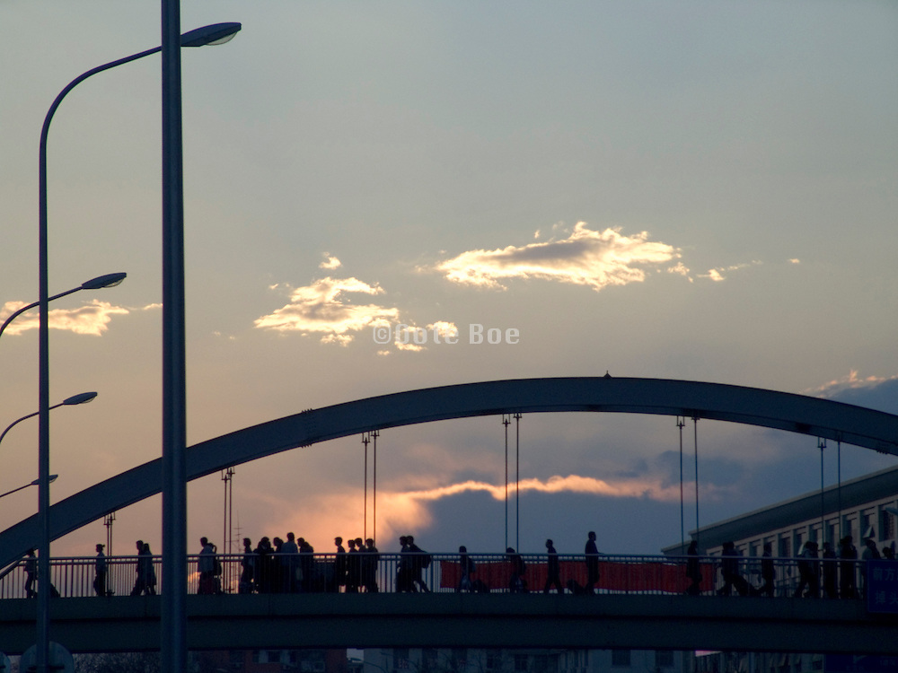 people crossing a bridge set against an colorful evening sky