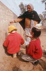 Primary school teacher teaching young children; using a wall as a whiteboard in Patiala; Punjab,