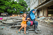 "12 DECEMBER 2012 - BANGKOK, THAILAND:  A demolition worker and her daughter at ""Washington Square"" a notorious entertainment district off Sukhumvit Soi 22 in Bangkok. Demolition workers on many projects in Thailand live on their job site tearing down the building and recycling what can recycled as they do so until the site is no longer inhabitable. They sleep on the floors in the buildings or sometimes in tents, cooking on gas or charcoal stoves working from morning till dark. Sometimes families live and work together, other times just men. Washington Square was one of Bangkok's oldest red light districts. It was closed early 2012 and is being torn down to make way for redevelopment.    PHOTO BY JACK KURTZ"