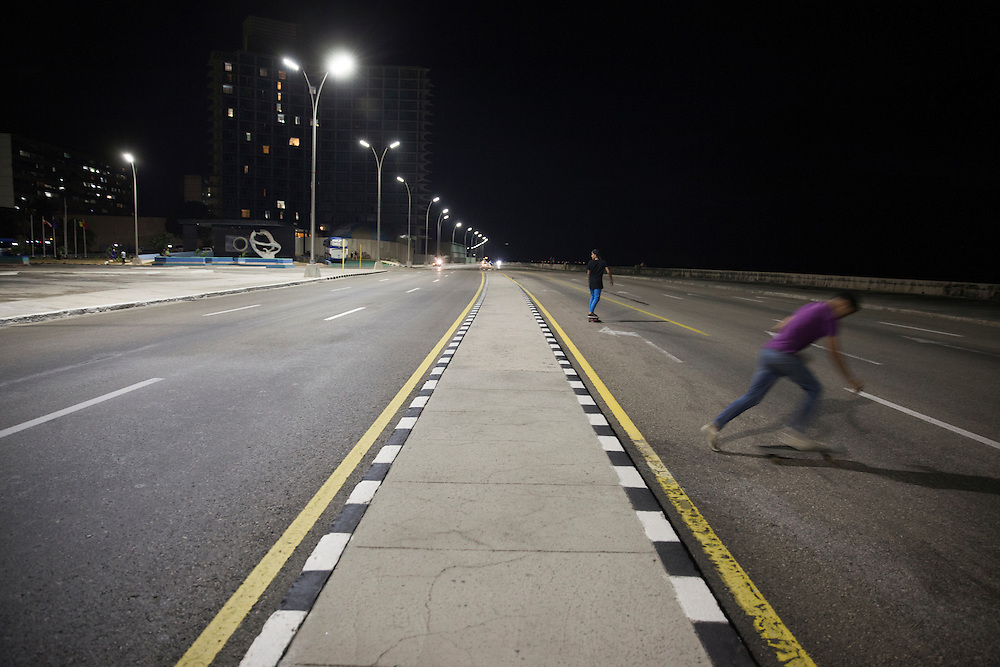 Teenagers practicing longboard tricks on the road at Malec&oacute;n in Havana, Cuba.<br /> <br /> J&oacute;venes practicando longboard por la noche en la carretera del Malec&oacute;n, en La Habana.