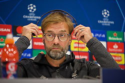 LIVERPOOL, ENGLAND - Tuesday, November 26, 2019: Liverpool's manager Jürgen Klopp puts on a set of headphones to listen to a translation during a press conference at Anfield ahead of the UEFA Champions League Group E match between Liverpool FC and SSC Napoli. (Pic by David Rawcliffe/Propaganda)