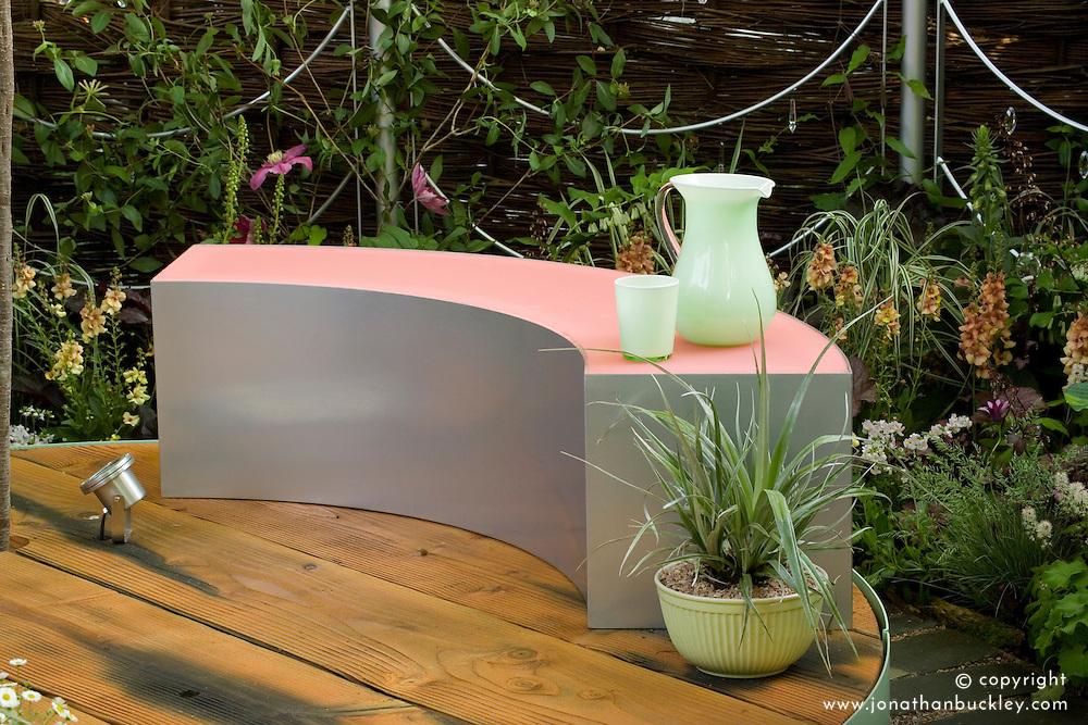 Silver and pink perspex bench on circular deck. The Crystal Cobweb Garden. Designer:  Freya Lawson - Chelsea 2005