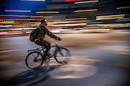 A long-exposure blurry photograph of a cyclist going through Nørrebro in Copenhagen.