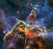 Hubble photo of a small portion of one of the largest known star-birth regions in the galaxy, the Carina Nebula. Three light-year-tall towers of cool hydrogen laced with dust rise from the wall of the nebula. Scorching radiation and fast winds (streams of charged particles) from super-hot newborn stars in the nebula are shaping and compressing the pillar, causing new stars to form within it. Streamers of hot ionized gas can be seen flowing off the ridges of the structure, and wispy veils of gas and dust, illuminated by starlight, float around its towering peaks. The denser parts of the pillar are resisting being eroded by radiation much like a towering butte in Utah's Monument Valley withstands erosion by water and wind.
