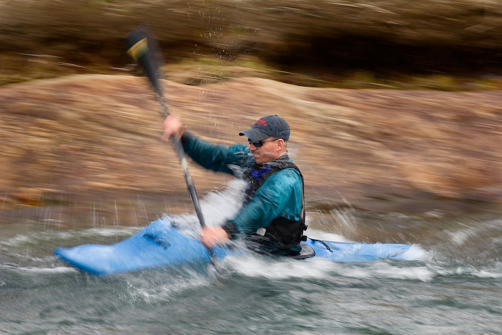 A kayaker paddles the Mad River in Waitsfield, Vermont.  The shot was panned to create the motion blur.