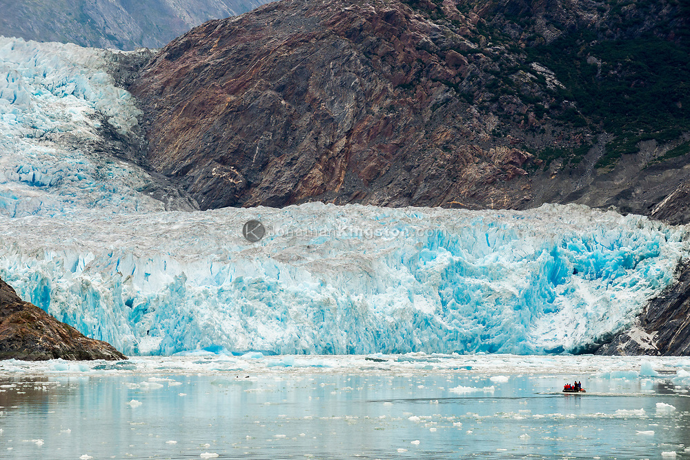 A small inflatable boat carries tourists close to the face of South Sawyer Glacier, Tracy Arm fjord, Alaska.