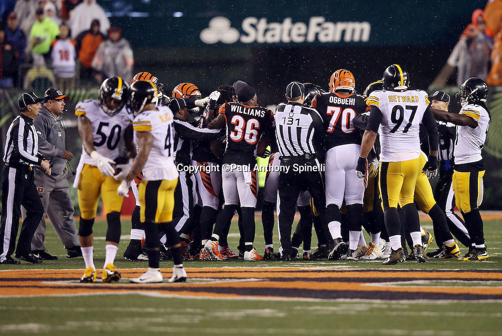NFL umpire Mark Pellis (131) and his crew members try to regain order and clear the field of unnecessary players and coaches after Cincinnati Bengals running back Giovani Bernard (25) gets hit hard by Pittsburgh Steelers inside linebacker Ryan Shazier (50) causing a third quarter fumble, recovered by Shazier, and starting a player melee over no penalty call for unnecessary roughness and leading with the helmet during the NFL AFC Wild Card playoff football game against the Pittsburgh Steelers on Saturday, Jan. 9, 2016 in Cincinnati. The Steelers won the game 18-16. (©Paul Anthony Spinelli)