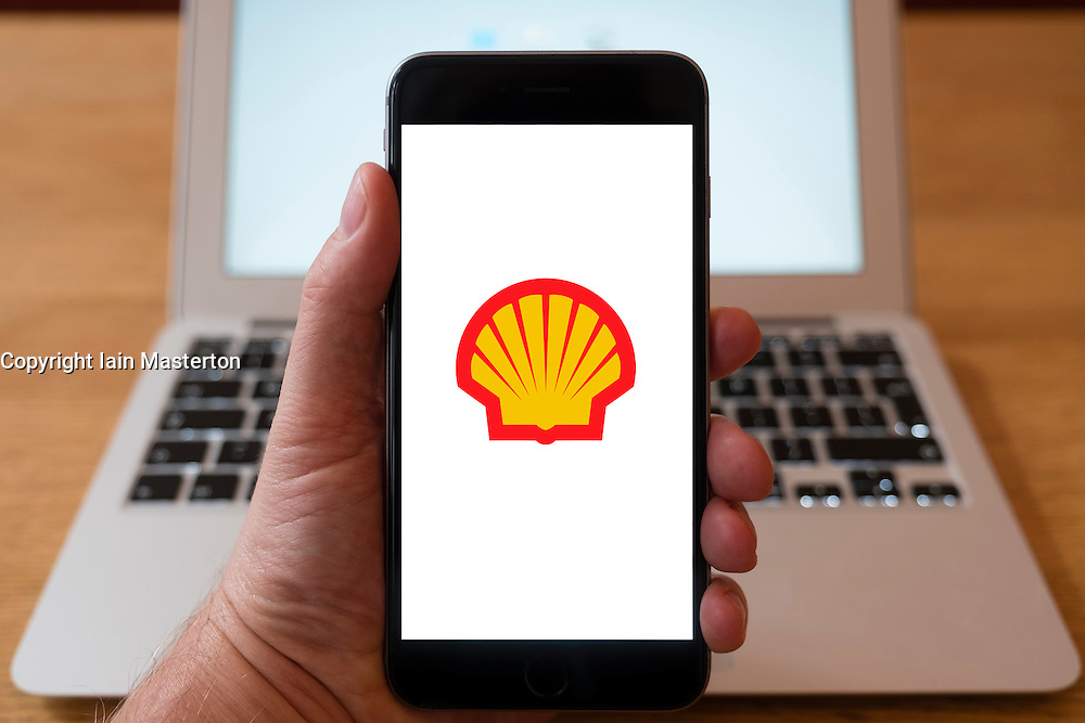 Using iPhone smartphone to display logo of Royal Dutch Shell oil and gas major