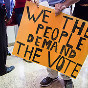 A concerned Charlotte resident holds a sign outside the main meeting chamber at the government center. Residents came to voice concerns over the selection process and many thought it was unfair that the new mayor would be appointed by city council and not put to a public vote.