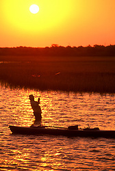 Stock photo of the silhouette of a man standing in the water and landing a fish at sunset