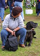 Eine Frau schaut gemeinsam mit ihrem grossen schwarzen Hund zu einer Veranstaltung im niedersächsischen Dannenberg hinüber.
