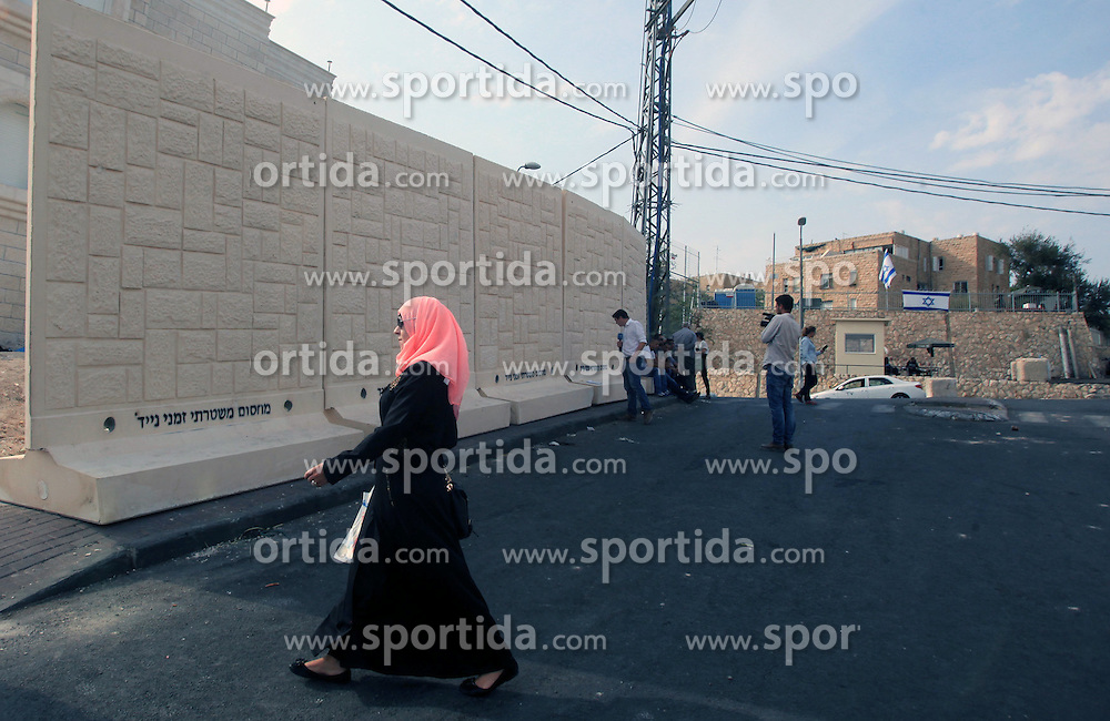 19.10.2015, Jerusalem, ISR, Gewalt zwischen Pal&auml;stinensern und Israelis, im Bild Kontrollen der Israelischen Sicherheitskr&auml;fte im Pal&auml;stinenser Gebiet // A Palestinian woman walks in front of a newly erected separation wall in Jerusalem's neighborhood of Jabal al-Mokaber on October 19, 2015. Israeli police began erecting a wall in east Jerusalem to protect a Jewish neighbourhood subject to firebomb and stone attacks launched from an adjacent Palestinian village, Israel on 2015/10/19. EXPA Pictures &copy; 2015, PhotoCredit: EXPA/ APAimages/ Mahfouz Abu Turk<br /> <br /> *****ATTENTION - for AUT, GER, SUI, ITA, POL, CRO, SRB only*****